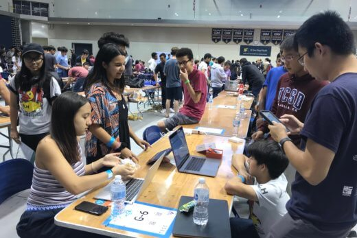 Crowded gymnasium filled with college-aged students at a hackathon.
